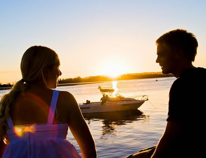 Couple sitting on the riverfront in front of boat