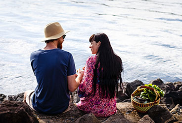 Couple sitting on river behind with farmers market produce in basket