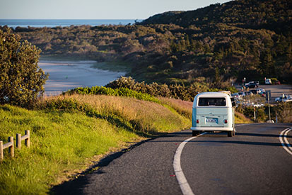 Kombi driving along Coast Road with views of Sharpes Beach