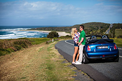 Couple leaning on car along Coast Road with beach in background
