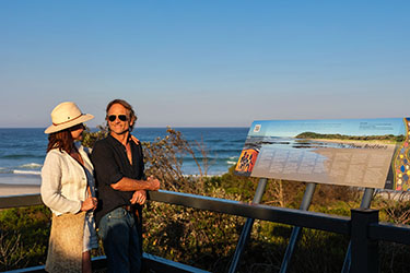 Couple looking at information sign overlooking beach