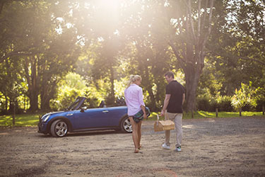 Couple with picnic basket walking towards convertible in hinterland