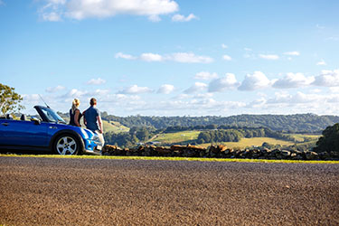 Couple leaning on car overlooking rural vista