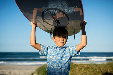 Boy carrying a surfboard on his head