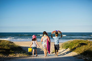 Three kids walking towards beach with buckets and boards