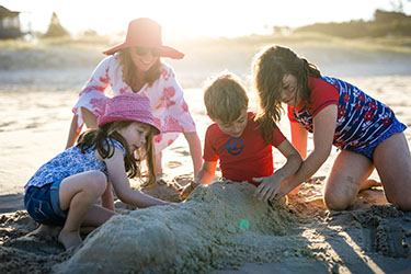 Kids and mum building a sandcastle