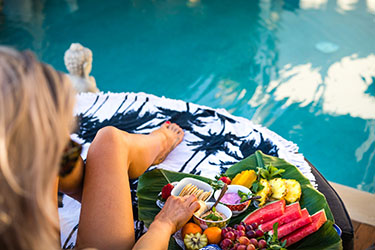 Lady sitting by pool with fruit platter