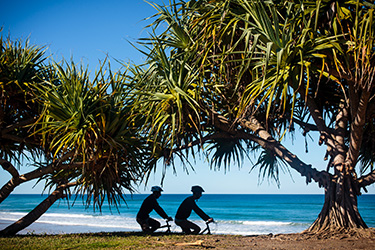 Bike riders under pandanus tree with Shelly Beach in background