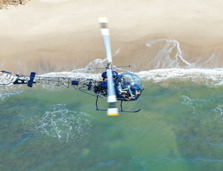 Helicopter flying over water. Photo Credit: Air T & G Helicopters