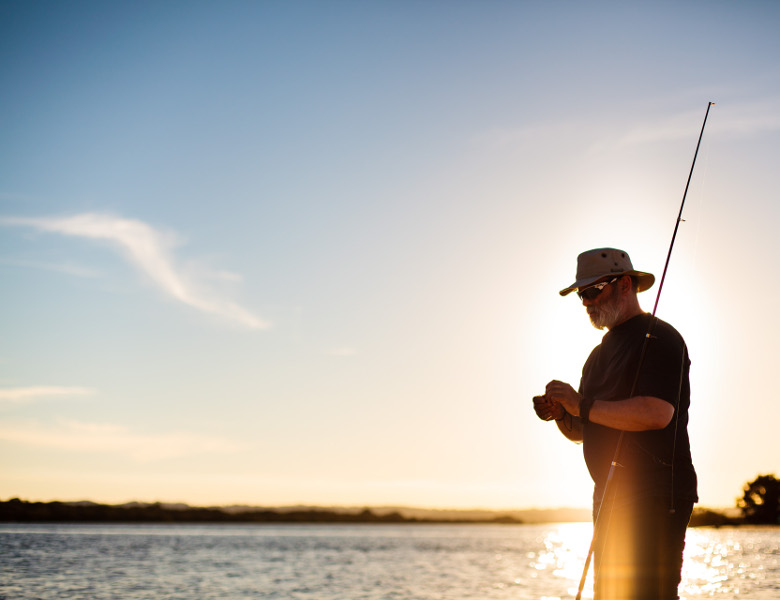 Man Fishing with sunset behind him