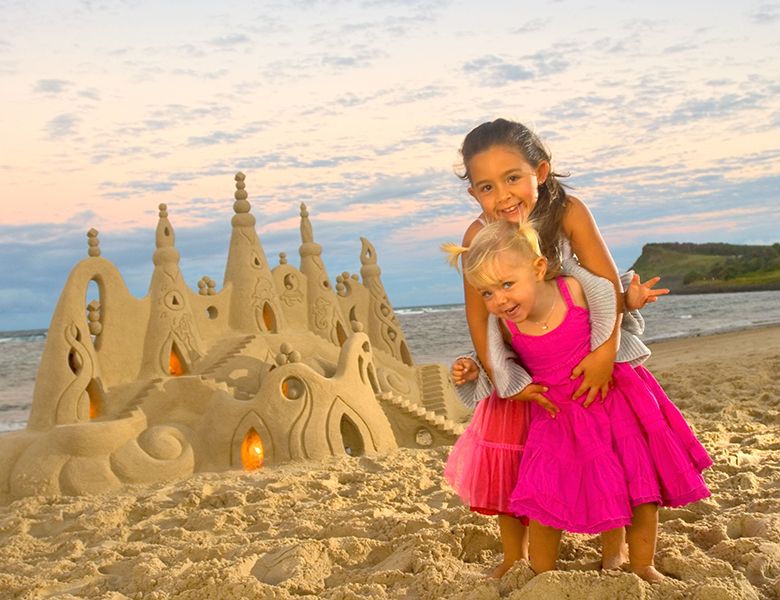 Girls building a sandcastle at the beach