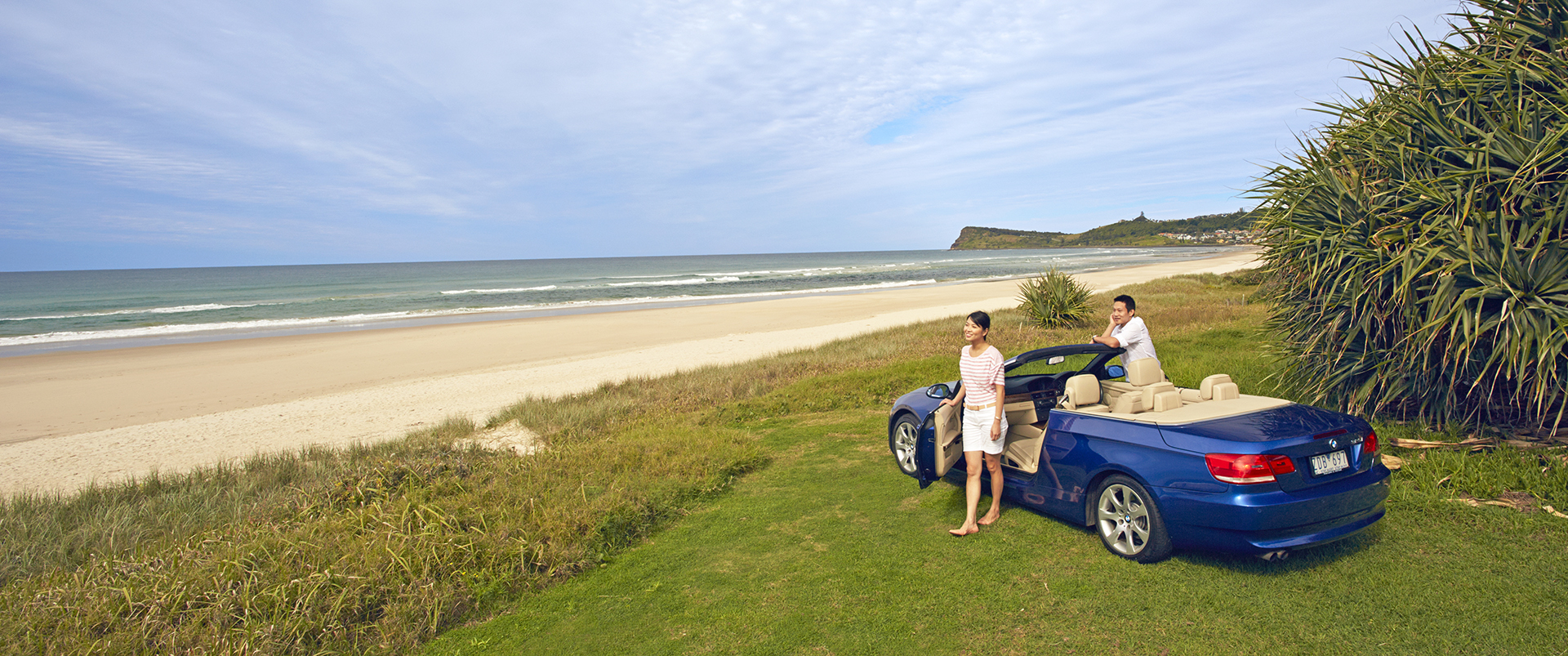 Tourism Australia image of couple with car overlooking Seven Mile Beach Lennox Headland